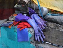 Rubber gloves for washing dishes bright red and purple color lie in a pile among household rags on a gray stone wall. Rubber gloves for washing dishes bright Stock Photos