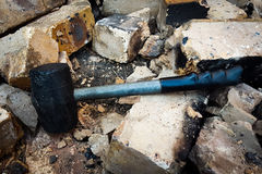 Rubber Hammer Demolish Bricks. Black Rubber Hammer that demolish and break down brick wall brown and concrete. Broken Pieces. Chunks of Bricks. Crumble down Royalty Free Stock Photography