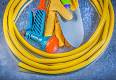 Rubber hand spraying garden hose protective gloves spade on meta. Llic surface gardening concept stock photos