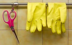 Rubber handskar och sax mot kök vägg Arkivbild