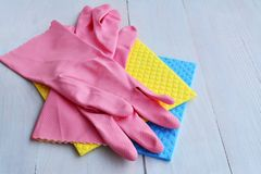 Rubber household gloves and absorbent sponge wipe-up clothes. For cleaning, dishwashing, housework and wipe away dirt dust over light painted wooden table royalty free stock photo