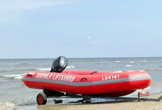 Rubber lifeguard boat trailer on sea shore Stock Photos