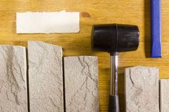 Rubber mallet and chisel. Rubber hammer and chisel on a background of stone cladding Royalty Free Stock Photos