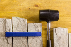 Rubber mallet and chisel. Rubber hammer and chisel on a background of stone cladding Royalty Free Stock Photo