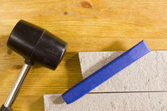 Rubber mallet and chisel. Rubber hammer and chisel on a background of stone cladding Royalty Free Stock Photography