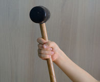 Rubber mallet in the hand of the child, on the wooden handle Royalty Free Stock Photos