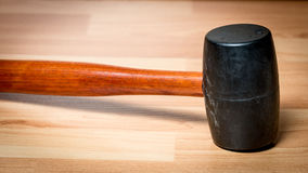 Rubber mallet side view on a wood surface. Side of a wood handled rubber mallet Stock Image