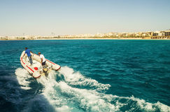 Rubber motor boat with two men at high speed sails by sea Stock Photos