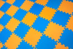 Rubber orange-blue colored floor puzzle. Horizontal layout perspective. Flooring indoors playground stock images