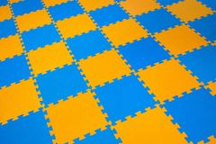 Rubber orange-blue colored floor puzzle. Horizontal layout perspective. Flooring indoors playground royalty free stock photo