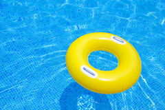 Rubber ring. Floating in transparent blue tiled pool Royalty Free Stock Photos