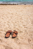 Rubber slippers on beach Stock Image