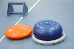 Rubber sport equipment fitballs and wooden stand in empty fitness room, different kinds of appliances for fitness. Healthy life stock photography