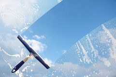 Rubber squeegee cleans a soaped window and clears a stripe of bl. Ue sky with clouds, concept for tranparency or spring cleaning, copy space in the background stock photos