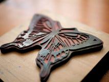 Rubber stämpel av fjärilen på träskrivbordet för konsthantverk royaltyfri fotografi