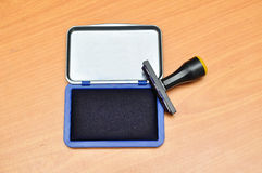 Rubber stamp on a blue pad Stock Photo