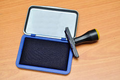 Rubber stamp on a blue pad. Image of rubber stamp on a blue pad Royalty Free Stock Images