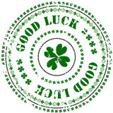 Rubber stamp: Good Luck. Illustration of a grunge rubber ink stamp on white background with four-leafed clovers, flowers and text: Good Luck Stock Image
