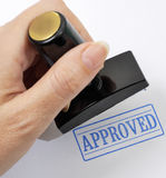 Rubber stamp in a han. D (on a light background Stock Photography