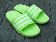 Rubber stripe slippers. On wooden background royalty free stock photo