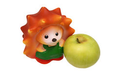 Rubber toy hedgehog and green apple. Stock Images