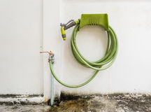 Rubber tube and water hose joined with faucet and rolled o Royalty Free Stock Photo