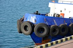 Tyre fender on tugbooat. Rubber tyre fender on blue tugbooat hul Royalty Free Stock Image