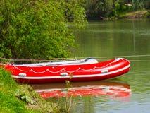Rubber uppblåsbart rött fartyg på flodkusten Arkivbild