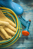 Rubber waterproof boots leather protective gloves garden hose on. Wooden board gardening concept royalty free stock images