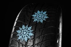 Rubber winter tire with snowflakes on dark background. Closeup stock photo