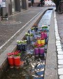 Rubberlaarzen in het water met bloemen in de stad van Freiburg Toeristische attractie stock fotografie