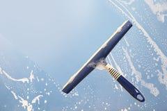 Rubberschuiver die een zeepachtig venster, de lente het schoonmaken blauw concept schoonmaken, Stock Afbeeldingen