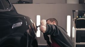 Rubbing black car to achieve perfect glance with a polishing mashine. Young male autocenter represantative. stock video footage