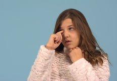 Rubbing an eye. Girl rubbing her itchy eye against a blue background. The girl was ten years old (tween) when the photo was taken stock image