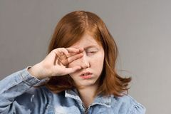 Rubbing eyes drowsy person. Sleepy drowsy read-haired young girl rub her right eye royalty free stock images