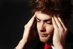 Rubbing his temples, stressed out. Low key image of a young man who looks stress out rubbing his temples Stock Photos