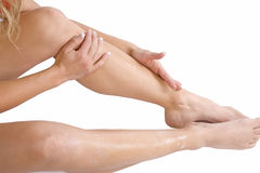 Rubbing lotion onto legs Stock Photography