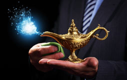 Rubbing magic Aladdins genie lamp. Businessman holding and rubbing a magic Aladdins genie lamp concept for business aspirations, hope and wishes Royalty Free Stock Image