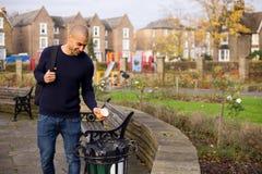 Rubbish bin. Man throwing rubbish in the bin in a park Royalty Free Stock Photos
