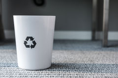 Rubbish bin with recycle logo. Indoors Royalty Free Stock Image
