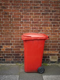 Rubbish bin. Red rubbish bin on pavement waiting for collection UK Royalty Free Stock Photos