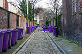 Rubbish bins lined up in narrow alley Stock Photos