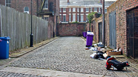 Rubbish bins lined up in narrow alley Royalty Free Stock Photo
