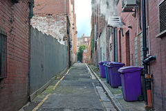 Rubbish bins lined up in narrow  alley Stock Images