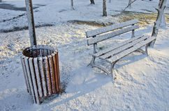 Rubbish box and wooden bench in winter park Stock Images