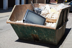 Rubbish container. With a discarded television Royalty Free Stock Photos