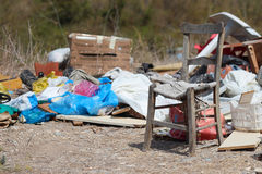 Rubbish dumped at side of road with chair. Royalty Free Stock Photography