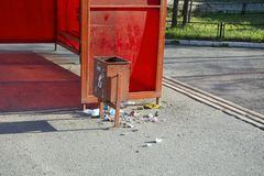 Rubbish dumped from the urn by hooligans at the bus stop.  royalty free stock photo