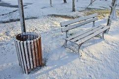 Rubbish la caja y el banco de madera en parque del invierno Imagenes de archivo