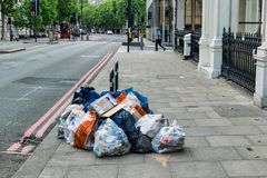 Rubbish on a London street. London, UK - May 30, 2019: Rubbish piled up on  side of a London street royalty free stock image